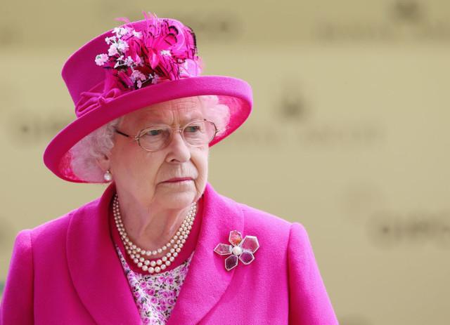 Queen Elizabeth wearing a brooch and pink hat.